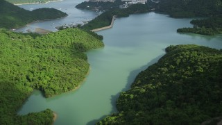 SS01_0064 - 5K stock footage aerial video fly over reservoir and tilt to reveal dam and apartment buildings by harbor on Hong Kong Island, China