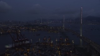 SS01_0115 - 5K stock footage aerial video fly over containers at the Port of Hong Kong toward center of Stonecutters Bridge at night in China