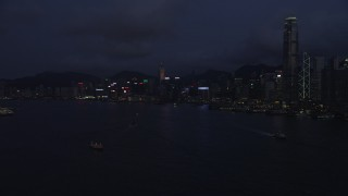 SS01_0129 - 5K stock footage aerial video approach Hong Kong Island skyline from the harbor at nighttime in China