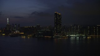 SS01_0157 - 5K stock footage aerial video approach Kowloon skyscraper overlooking Victoria Harbor at night, Hong Kong, China