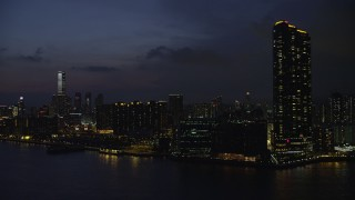 SS01_0158 - 5K stock footage aerial video of Harbourfront Landmark skyscrapers and waterfront apartment buildings at night in Kowloon, Hong Kong, China