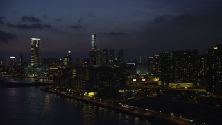 SS01_0160 - 5K stock footage aerial video of waterfront apartment buildings and view of tall towers at night in Kowloon, Hong Kong, China