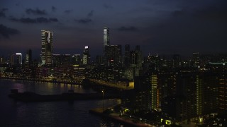 SS01_0161 - 5K stock footage aerial video of waterfront hotels near The Masterpiece skyscrapers at night in Kowloon, Hong Kong, China