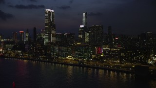 SS01_0162 - 5K stock footage aerial video flyby waterfront hotels with blinking lights near The Masterpiece tower at night in Kowloon, Hong Kong, China