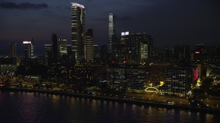 SS01_0163 - 5K stock footage aerial video of hotel overlooking the harbor near The Masterpiece at night in Kowloon, Hong Kong, China