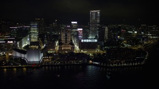 SS01_0189 - 5K stock footage aerial video approach waterfront concert hall, museum and towers at night in Kowloon, Hong Kong, China
