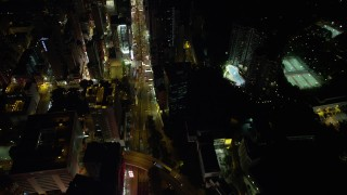 SS01_0196 - 5K stock footage aerial video of following Nathan Road between office and apartment buildings at night in Kowloon, Hong Kong, China