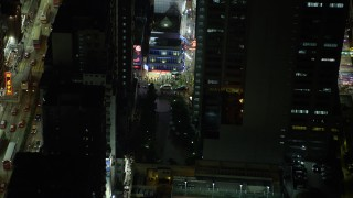 SS01_0209 - 5K stock footage aerial video a slow reverse from corner shop at night in Kowloon, Hong Kong, China