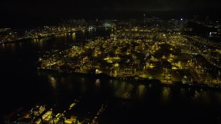 SS01_0233 - 5K stock footage aerial video fly over cargo ships and cranes at the Port of Hong Kong at night, China