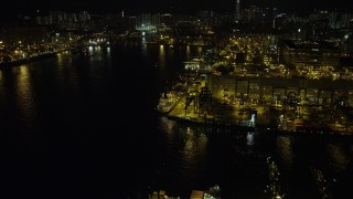 SS01_0236 - 5K stock footage aerial video fly over ships docked under cranes at night at the Port of Hong Kong, China
