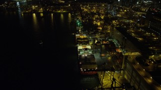 SS01_0237 - 5K stock footage aerial video fly over a row of cargo ships docked at the Port of Hong Kong at nighttime, China