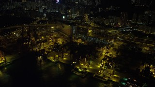 SS01_0239 - 5K stock footage aerial video of cargo cranes at the Port of Hong Kong at night, China