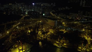 SS01_0240 - 5K stock footage aerial video flyby cargo cranes and wide streets at the Port of Hong Kong at night, China