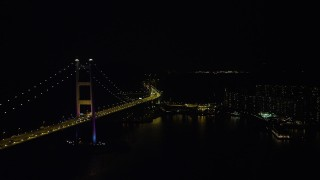 SS01_0245 - 5K stock footage aerial video of flying between the Tsing Ma Bridge and waterfront apartment buildings at night in Hong Kong, China