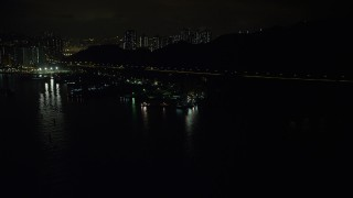 SS01_0251 - 5K stock footage aerial video approach poorly lit piers and warehouses on Rambler Channel at night in Hong Kong, China