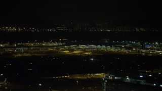 SS01_0279 - 5K stock footage aerial video of airliners parked at the terminal at Hong Kong International Airport at night, China