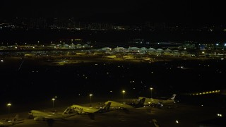 SS01_0280 - 5K stock footage aerial video of Hong Kong International Airport Terminals at night, and tilt to parked airliners, China