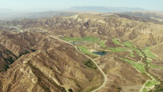 TS01_008 - 1080 stock footage aerial video approach golf course and brown hills in Simi Valley, California