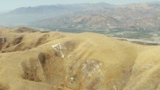 TS01_013 - 1080 stock footage aerial video of fly over hills to reveal farmland in Piru, California