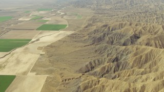 TS01_041 - 1080 stock footage aerial video pan from mountains to reveal farm fields, Cuyama Valley, California
