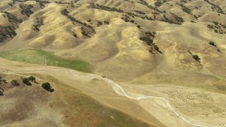 TS01_063 - 1080 aerial stock footage video of of a dry creek, and road through hills in Paso Robles, California