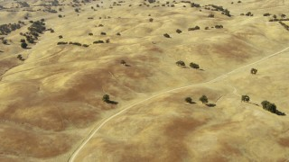 TS01_069 - 1080 stock footage aerial video of flying over dirt road and hills in Paso Robles, California