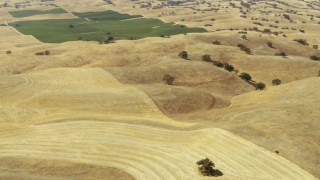 TS01_072 - 1080 stock footage aerial video of rolling hills toward farmland, Paso Robles, California