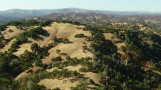 TS01_120 - 1080 stock footage aerial video of flying over hills to reveal a lake near Morgan Hill, California