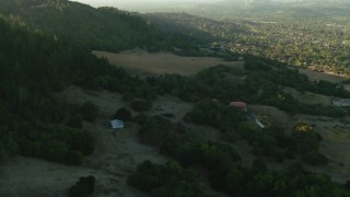 TS01_196 - 1080 stock footage aerial video of flying over hills and barn to homes in Bennett Valley, California