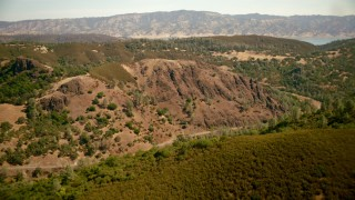 TS01_253 - 1080 stock footage aerial video of flying over mountain ridges and road toward Lake Berryessa, California