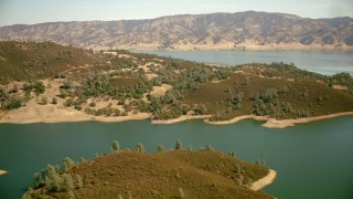 TS01_256 - 1080 stock footage aerial video of flying over the shore of Lake Berryessa toward mountains in California