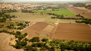 TS01_265 - 1080 stock footage aerial video of flying over farm fields and barns in Capay, California