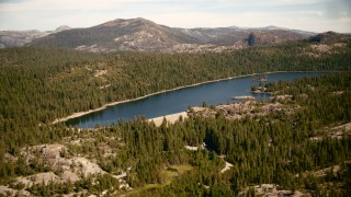 TS01_292 - 1080 stock footage aerial video fly over trees to approach the Lake Valley Reservoir, Sierra Nevada Mountains, California
