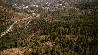 TS01_294 - 1080 stock footage aerial video flyby train tracks, tilt to reveal mountain highway, Sierra Nevada Mountains, California
