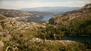 TS01_301 - 1080 stock footage aerial video fly over smaller lake and lodge toward Donner Lake, California
