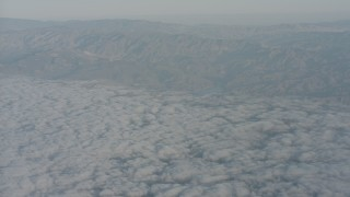 WA001_017 - 4K stock footage aerial video tilt from clouds to reveal and approach mountain range in Santa Clarita Valley, California