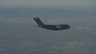 WA001_043 - 4K stock footage aerial video zoom in on a Boeing C-17 flying over Solano County, California