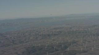 WA001_050 - 4K stock footage aerial video air-to-air view of a jet flying near Suisun Bay and windmills in Solano County, California