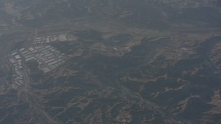 WA002_010 - 4K stock footage aerial video reverse view of hillside homes and warehouse buildings in Castaic, California