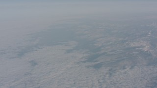 WA002_044 - 4K stock footage aerial video tilt up from a blanket of white clouds to reveal snow Sierra Nevada Mountain, California