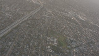 WA003_024 - 4K stock footage aerial video pan across neighborhoods to reveal I-105 with heavy traffic in Lynwood, California