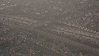 WA003_026 - 4K stock footage aerial video pan across I-105 to reveal the Lear jet landing gear as the plane approaches Hawthorne Airport, California