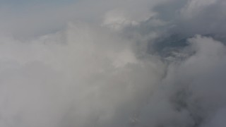 WA004_081 - 4K stock footage aerial video of tilting from snowy mountain ridges to approach clouds in Washington