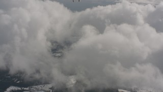 WA004_089 - 4K stock footage aerial video tilt from bird's eye of forest and snow to reveal clouds in Washington
