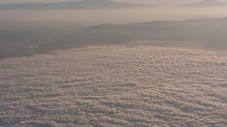 WA005_012 - 4K stock footage aerial video approach mountains at sunset, and tilt to clouds below in Southern California