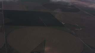 WA005_027 - 4K stock footage aerial video fly through clouds to reveal farms and circular crop fields in Kansas