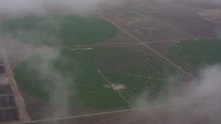 WA005_028 - 4K stock footage aerial video flyby clouds to reveal circular crop fields in Kansas