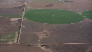 WA005_031 - 4K stock footage aerial video of a reverse view of flying through clouds to reveal circular crop fields in Kansas