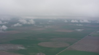 WA005_035 - 4K stock footage aerial video fly into the clouds above circular crop fields in Kansas