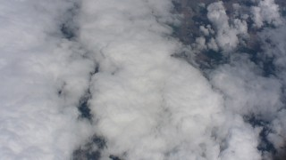 WA005_055 - 4K stock footage aerial video of a wide view of patchy clouds over farmland, tilt to denser clouds below in Kansas